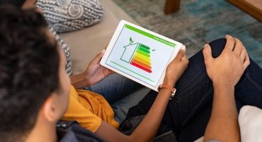 rear view of couple viewing energy efficiency status on a tablet