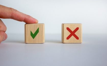 two wooden blocks with a green checkmark and a red x with a finger pointing to the green checkmark for choosing the right contractor