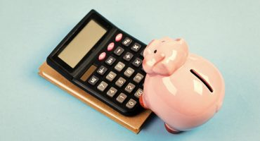 piggy bank using calculator to determine cost of bathroom model