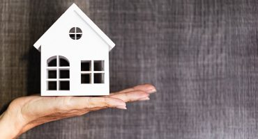 Hand holding a house model. Real estate agent offer house, property insurance and security. Buy and rent house concept. Grey background.